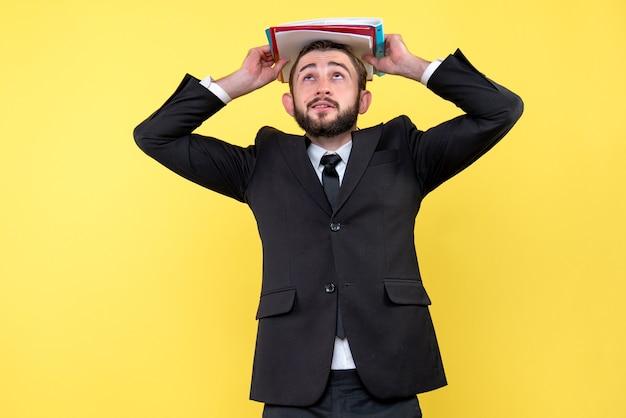 Widok z przodu biznesmen młody człowiek patrząc i trzymając foldery na czubku głowy na żółto