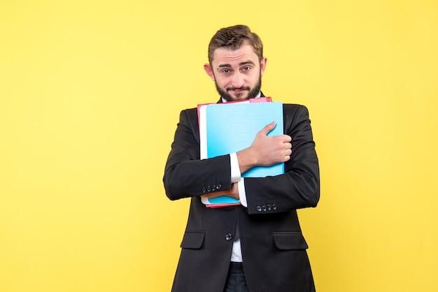 Widok z przodu biznesmen młody człowiek patrząc pewnie i trzymając foldery na żółto
