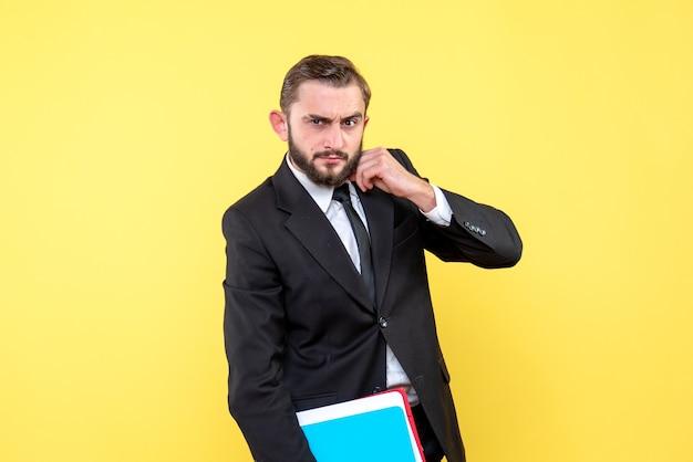 Widok z przodu biznesmen młody człowiek patrząc tęsknie i trzymając foldery na żółto