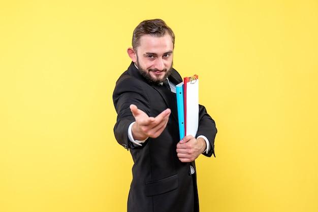 Widok z przodu biznesmen młody człowiek wyciąga jedną ręką i trzymając foldery z innym na żółto