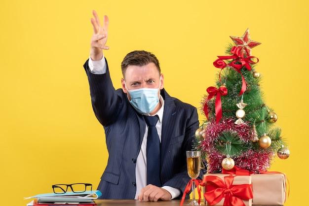 Widok z przodu biznesmena krzyczącego na kogoś siedzącego przy stole w pobliżu choinki i przedstawia na żółto