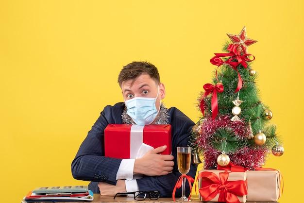 Widok z przodu biznesmena trzymającego prezent szczelnie siedzi przy stole w pobliżu choinki i przedstawia na żółto