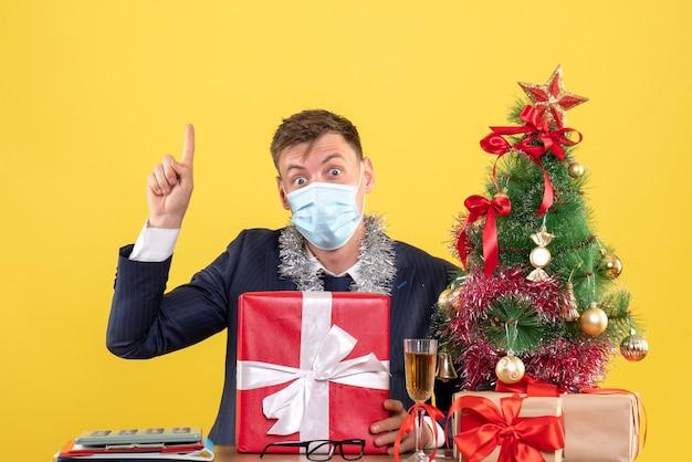 Widok z przodu biznesmena z prezentem świątecznym siedzi przy stole w pobliżu choinki i przedstawia na żółto