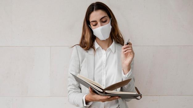 Widok z przodu bizneswoman z maską i porządkiem obrad