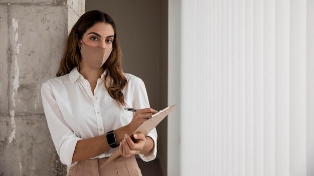 Widok z przodu bizneswoman z maską i schowkiem