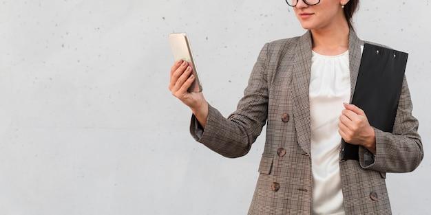 Widok z przodu bizneswoman z smartphone i notatnika na zewnątrz