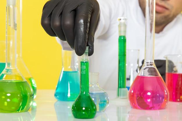 Widok z przodu bliżej młody chemik mężczyzna w białym garniturze przed stołem z kolorowymi roztworami, trzymając kolbę na żółtym biurku laboratorium pracy naukowej