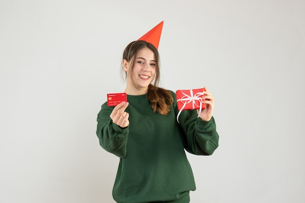 Widok z przodu błoga dziewczyna z czapką z przyjęciem, trzymając prezent i kartę