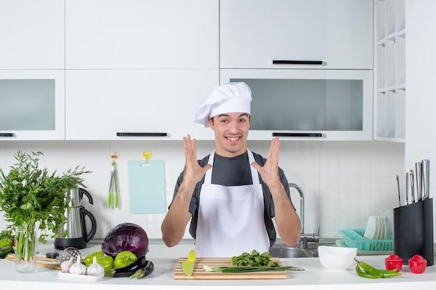 Widok z przodu błogi młody szef kuchni w mundurze