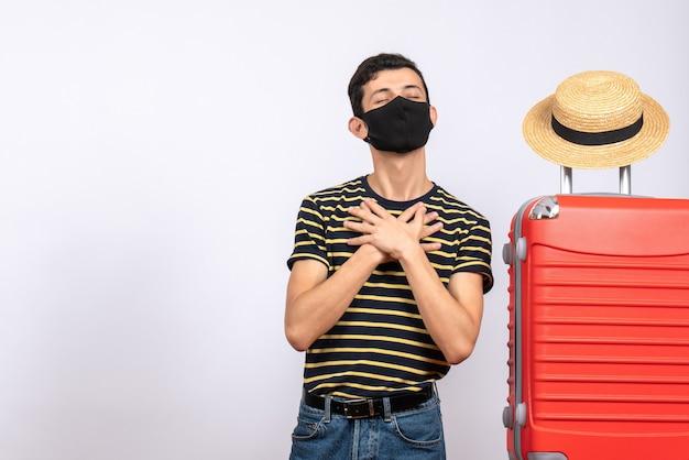Widok z przodu błogi młody turysta z czarną maską stojący w pobliżu czerwonej walizki