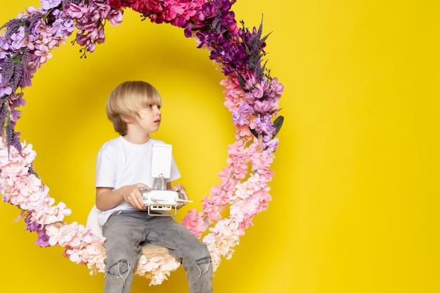 Widok z przodu blond chłopiec śliczna urocza blondynka z włosami siedząca na kwiatku stała na żółtej przestrzeni