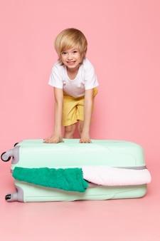 Widok z przodu blond chłopiec urocza śliczna stojąca na niebieskiej torbie na różowo