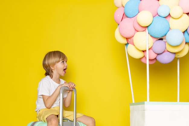 Widok z przodu blond chłopiec w białej koszulce i żółtych szortach wraz z kolorowymi balonami na żółtym