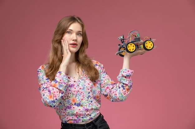 Widok z przodu blond dama zaskakująca dziwną zabawką samochodową