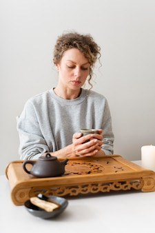 Widok z przodu blond kobiety z kręconymi włosami, picie herbaty i relaks