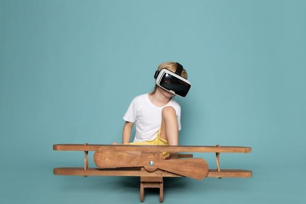 Widok z przodu blondynka chłopiec grający w gogle vr w białej koszulce na niebieskim biurku