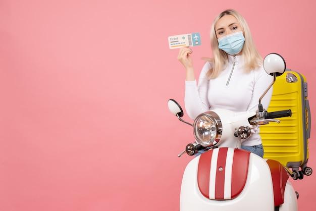 Widok z przodu blondynka młoda dama na motorowerze z żółtą walizką trzymając bilet