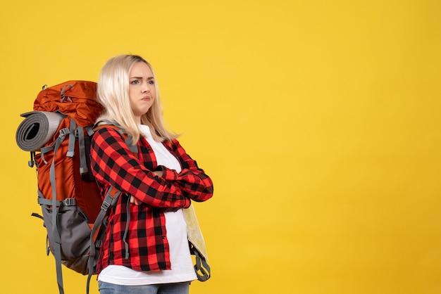 Widok z przodu blondynka podróżnik kobieta z plecakiem skrzyżowane ręce, stojąc na żółtej ścianie