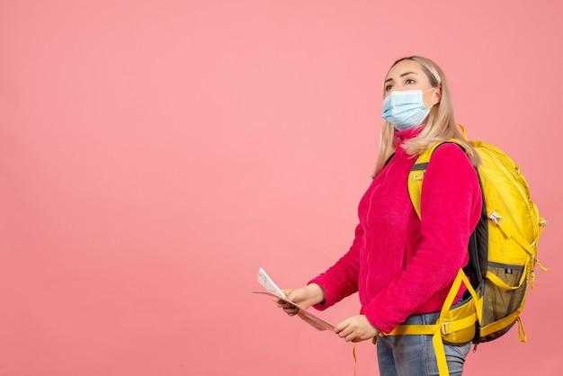 Widok z przodu blondynka podróżnik kobieta z żółtym plecakiem na sobie maskę trzymając mapę