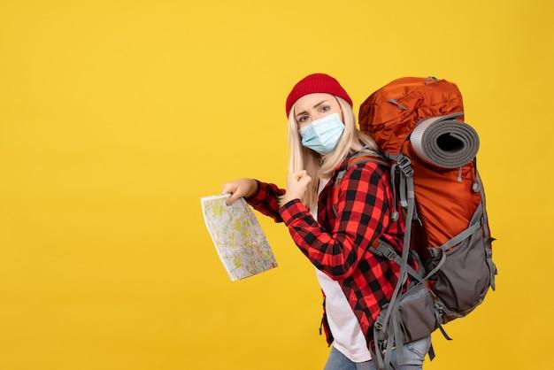 Widok z przodu blondynka z jej czerwonym plecakiem trzymając mapę