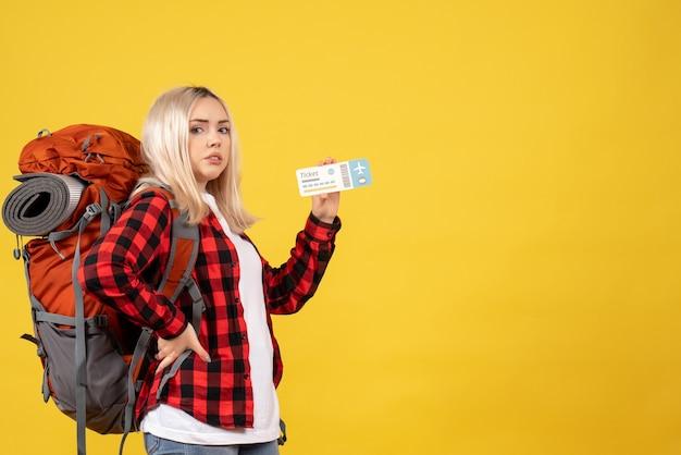 Widok z przodu blondynka z jej plecakiem trzymając bilet kładąc rękę na talii