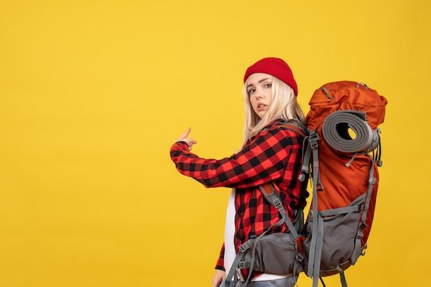 Widok z przodu blondynka z plecakiem, wskazując na tył