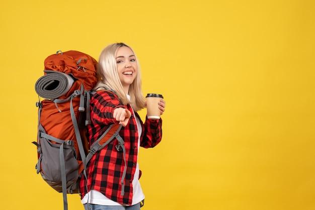 Widok z przodu blondynka z plecakiem wskazującym z przodu, wskazując palcami z przodu