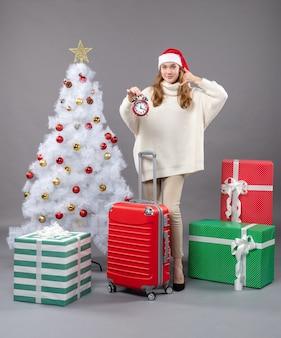 Widok z przodu blondynka z santa hat trzyma czerwony budzik pokazujący zadzwoń do mnie znak telefonu