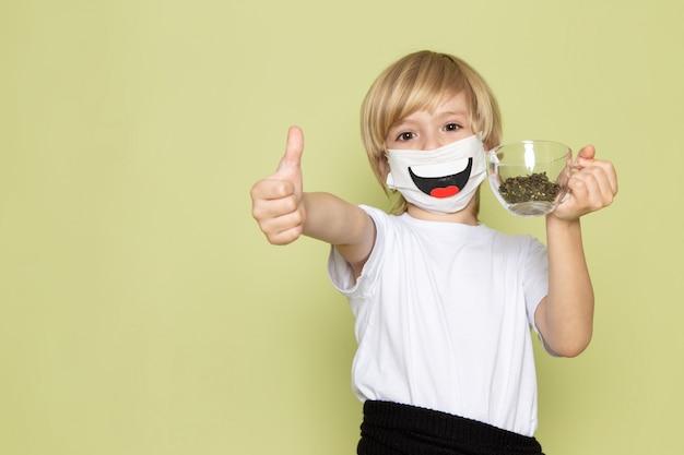 Widok z przodu blondynki uśmiechnięty chłopiec w białej koszulce i zabawnej masce trzymającej gatunki na biurku w kolorze kamienia