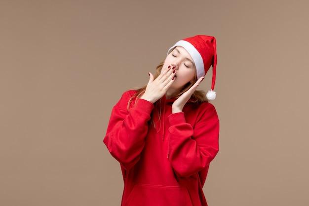 Widok z przodu boże narodzenie dziewczyna próbuje spać na brązowym tle świąteczne emocje świąteczne