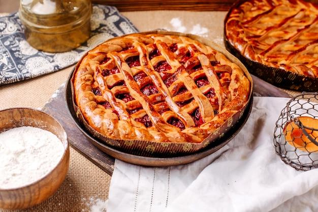 Widok z przodu brązowe ciasto wiśniowe smaczne słodkie pyszne na jasnej podłodze