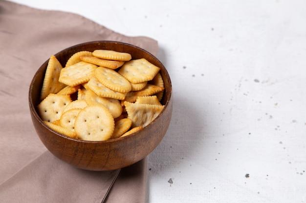 Widok z przodu brązowego talerza z solonymi smacznymi krakersami i chipsami na jasnej powierzchni