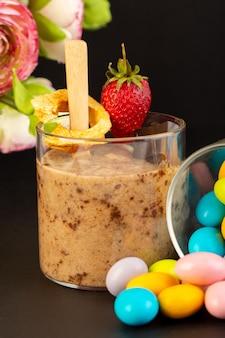 Widok z przodu brązowy deser czekoladowy smaczne pyszne słodkie ze sproszkowanym kawowym batonikiem czekoladowym i cukierkami truskawkowymi na ciemnym tle słodki deser odświeżający