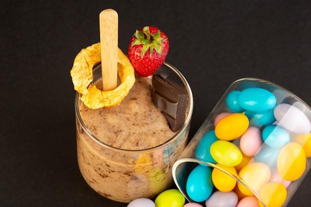 Widok z przodu brązowy deser czekoladowy smaczne pyszne słodkie ze sproszkowanym kawowym batonikiem czekoladowym i truskawką z cukierkami na ciemnym tle słodki deser odświeżający