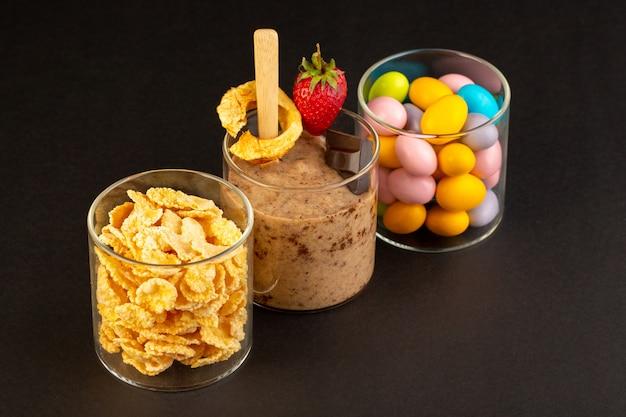 Widok z przodu brązowy deser czekoladowy smaczne pyszne słodkie ze sproszkowanym kawowym batonikiem czekoladowym i truskawką z płatkami kukurydzianymi i cukierkami na ciemnym tle słodki deser odświeżający