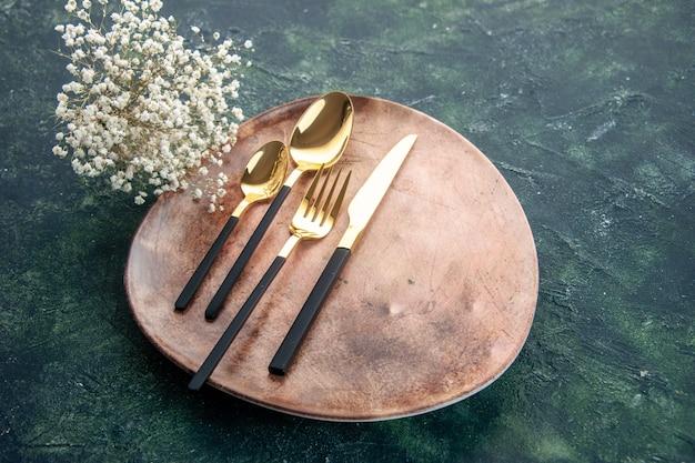 Widok z przodu brązowy talerz ze złotymi sztućcami na ciemnoniebieskim tle