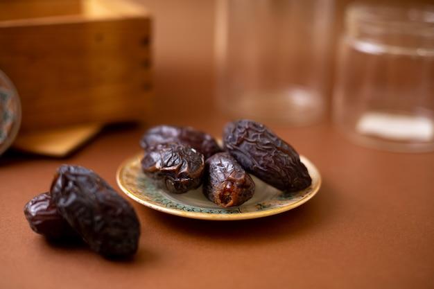 Widok z przodu brązowy xurma cały słodki talerz wewnętrzny na brązowej powierzchni drewnianej