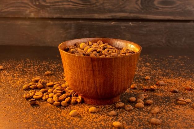 Widok z przodu brązowych nasion kawy wewnątrz brązowej płytki na brązowych nasionach kawy