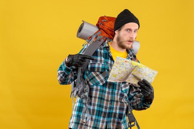 Widok z przodu brodaty młody turysta ze skórzanymi rękawiczkami i plecakiem, wskazując na mapę