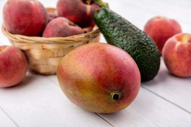 Widok z przodu brzoskwiń na wiadrze z awokado mango na białej powierzchni