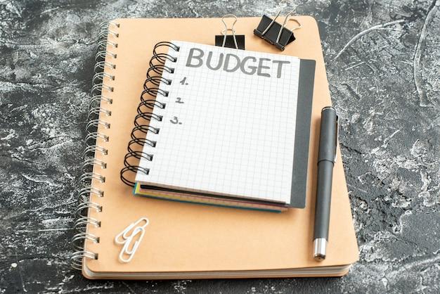 Widok z przodu budżet pisemna uwaga na notatnik z piórem na ciemnym tle