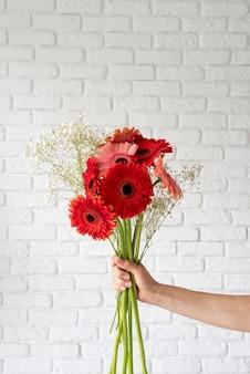 Widok z przodu bukietu kwiatów trzymanych przez kobiecą rękę
