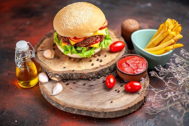 Widok z przodu burger mięsny z frytkami na ciemnym tle