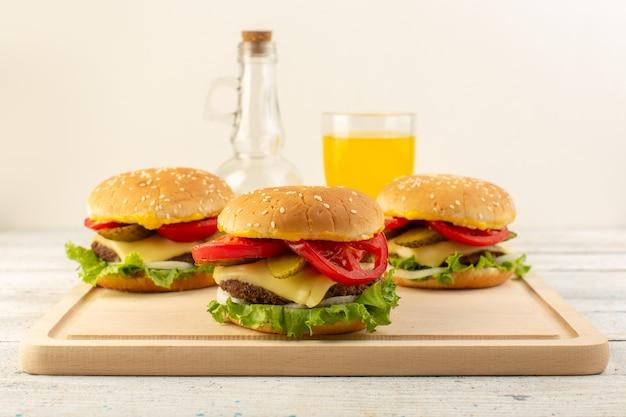 Widok z przodu burgery z kurczaka z serem, sokiem z zielonej sałaty i oliwą z oliwek na drewnianym biurku i kanapkę z jedzeniem fast-food