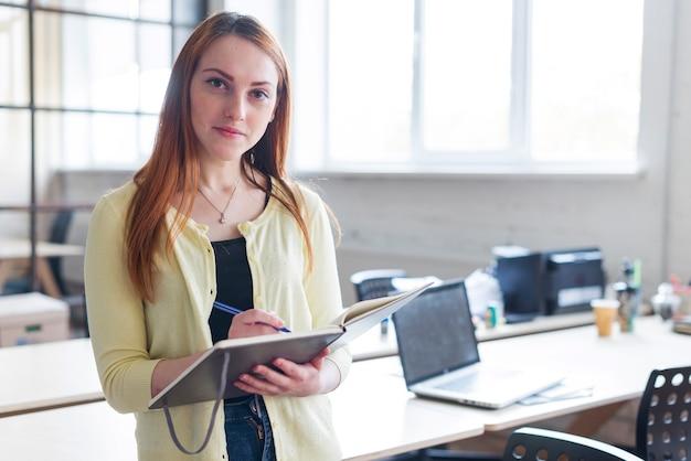 Widok z przodu businesswoman gospodarstwa notatnik i długopis patrząc na kamery