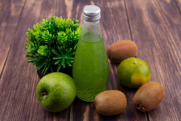 Widok z przodu butelka soku z jabłkiem mandarynki i kiwi na drewnianej ścianie