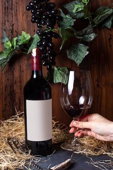 Widok z przodu butelki czerwonego wina z czerwonym winem wraz z czarnymi winogronami i zielonymi liśćmi na szarym napoju alkoholowym z winnicy