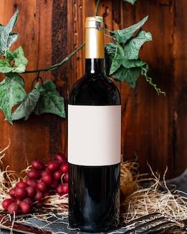 Widok z przodu butelki czerwonego wina ze złotą nakrętką wraz z jagodami i zielonymi liśćmi na tle winnicy alkoholowej