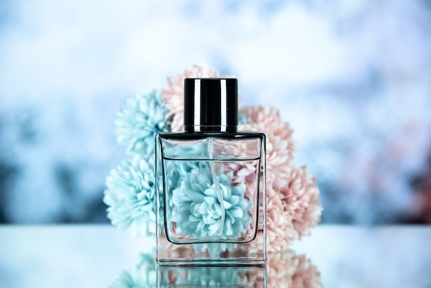 Widok z przodu butelki perfum i kwiatów na jasnoniebieskim rozmytym tle