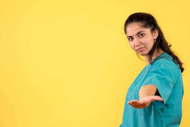 Widok z przodu całkiem kobiet lekarza, podając rękę na żółtej ścianie
